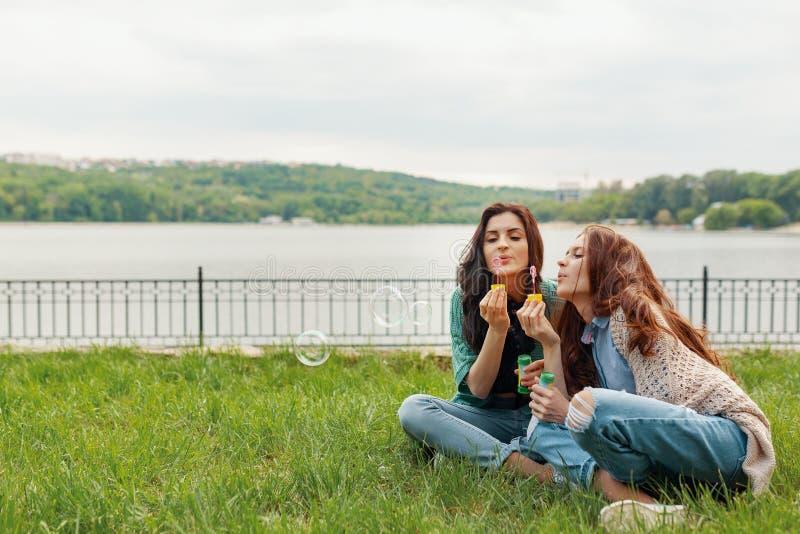 Duas irmãs que têm o divertimento ao fazer bolhas e ao sentar-se no g imagens de stock royalty free