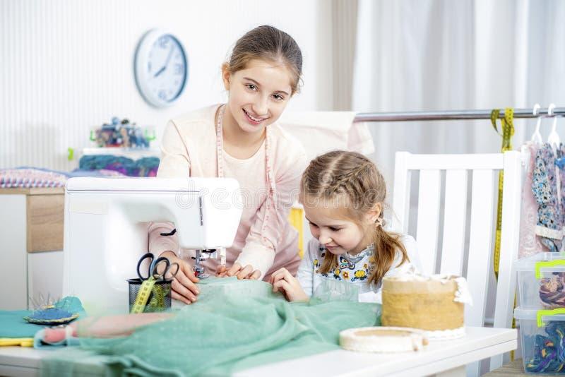 Duas irmãs que trabalham em uma máquina de costura foto de stock