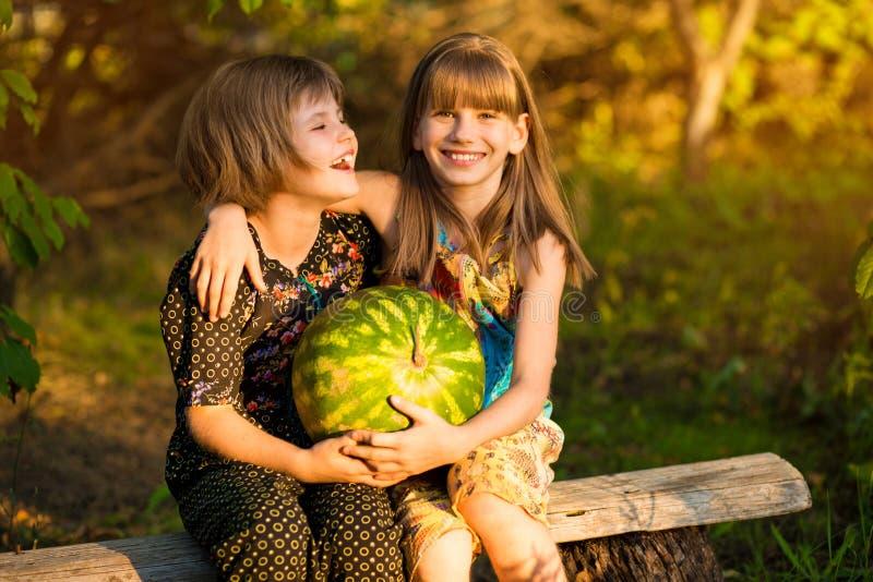 Duas irm?s mais nova engra?adas que comem a melancia fora no dia de ver?o morno e ensolarado Alimento biol?gico saud?vel imagens de stock
