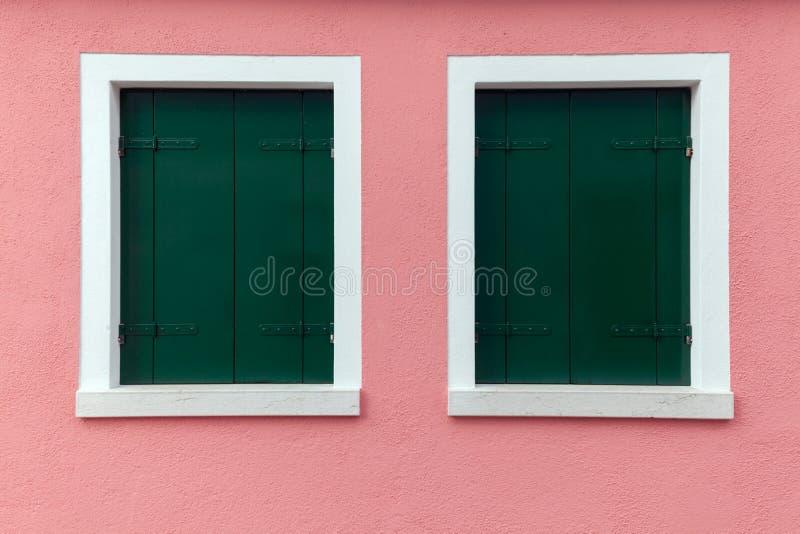 Duas janelas velhas com obscuridade - obturadores verdes na luz - parede cor-de-rosa fotografia de stock royalty free
