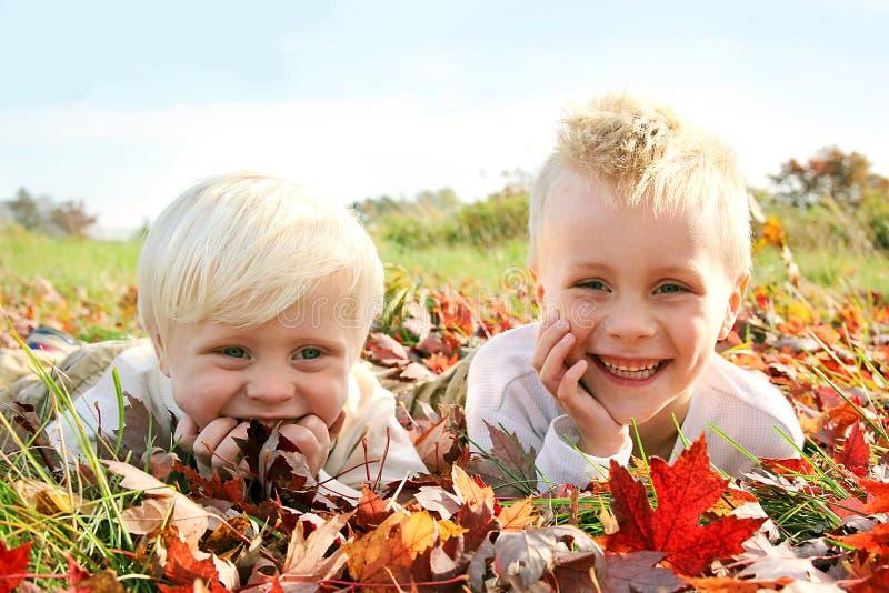 Duas jovens crianças felizes que jogam fora nas folhas da queda imagens de stock royalty free