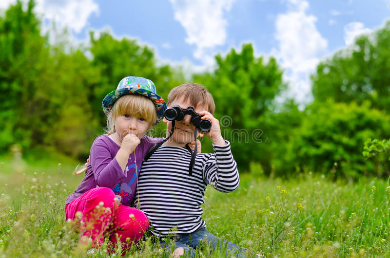 Duas jovens crianças que jogam com binóculos imagens de stock
