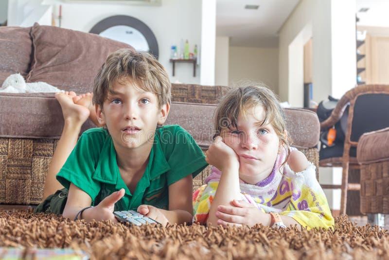 Duas jovens crianças que olham a tevê imagem de stock