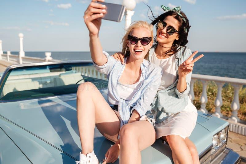 Duas jovens mulheres alegres que sentam-se no carro e que tomam o selfie foto de stock royalty free