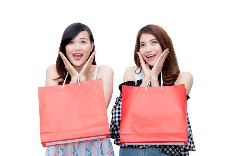 Duas jovens mulheres asiáticas de sorriso bonitas com venda da compra ensacam foto de stock