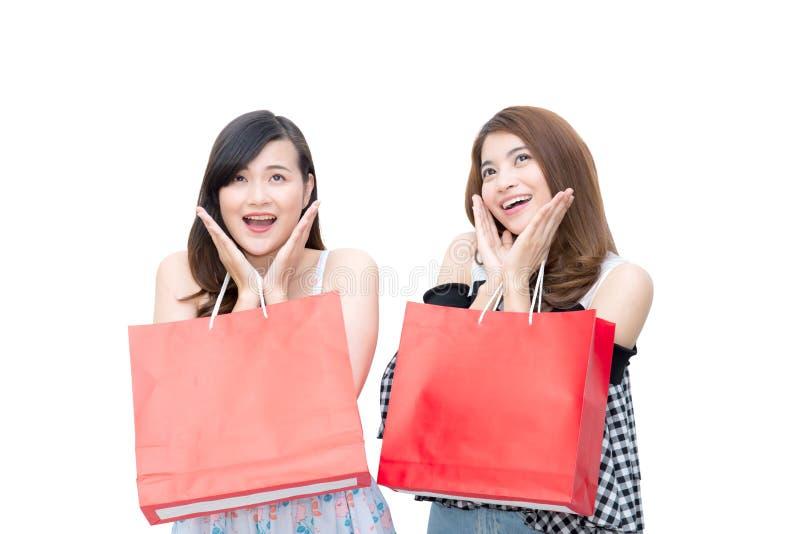 Duas jovens mulheres asiáticas de sorriso bonitas com venda da compra ensacam fotos de stock royalty free