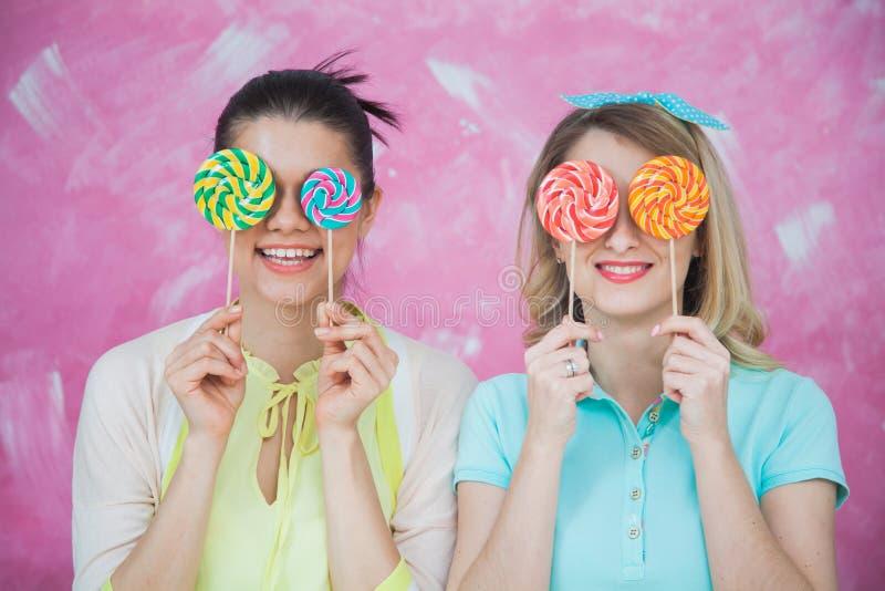 Duas jovens mulheres atrativas com pirulitos dos doces imagens de stock royalty free