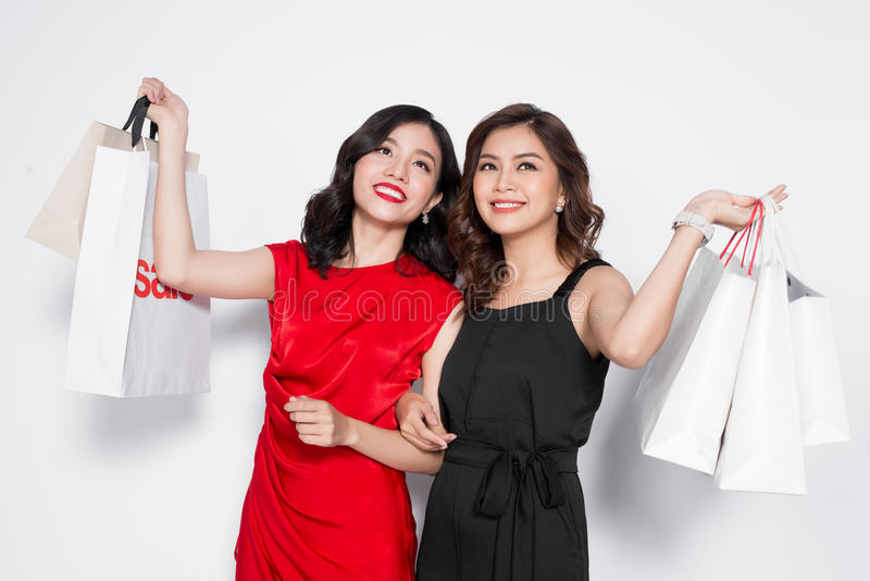 Duas jovens mulheres atrativas felizes com os sacos de compras no CCB branco fotografia de stock royalty free