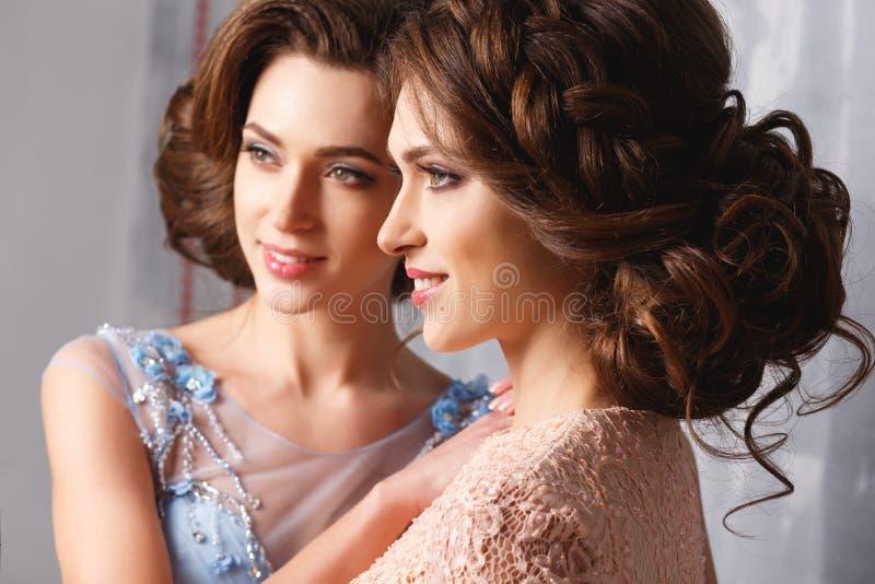 Duas jovens mulheres bonitas dos gêmeos em vestidos luxuosos, cores pastel foto de stock royalty free