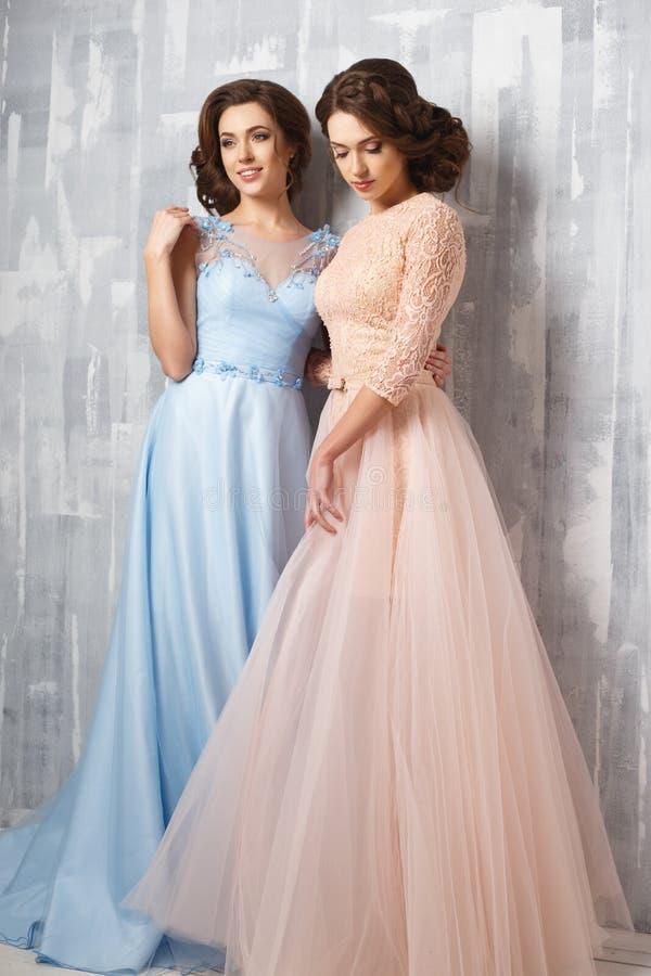Duas jovens mulheres bonitas dos gêmeos em vestidos luxuosos, cores pastel fotos de stock royalty free
