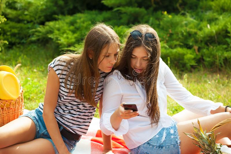 Duas jovens mulheres bonitas em um piquenique que olha a tela do smartphone imagens de stock