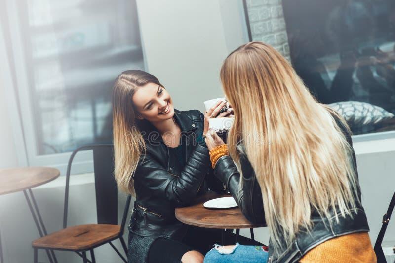 Duas jovens mulheres bonitas na roupa da forma que tem o resto que falam e café bebendo no restaurante exterior fotos de stock royalty free