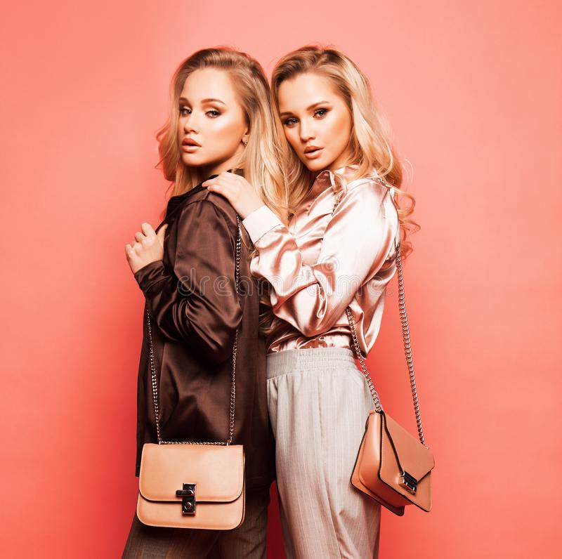 Duas jovens mulheres bonitas na roupa ocasional que levanta sobre o fundo cor-de-rosa fotografia de stock