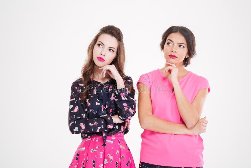 Duas jovens mulheres bonitas pensativas que estão e que pensam imagem de stock
