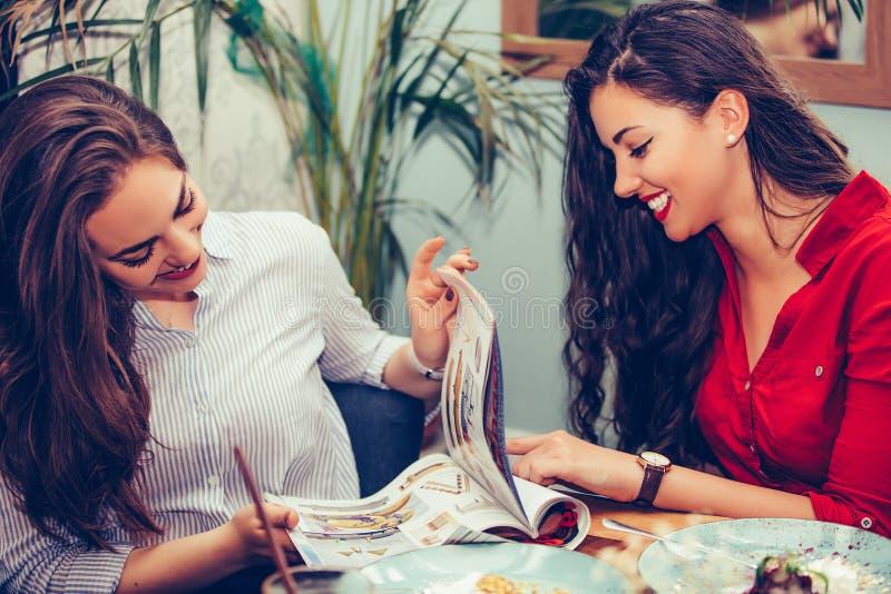 Duas jovens mulheres bonitas que apreciam o bolo junto ao ler o compartimento no caf? foto de stock