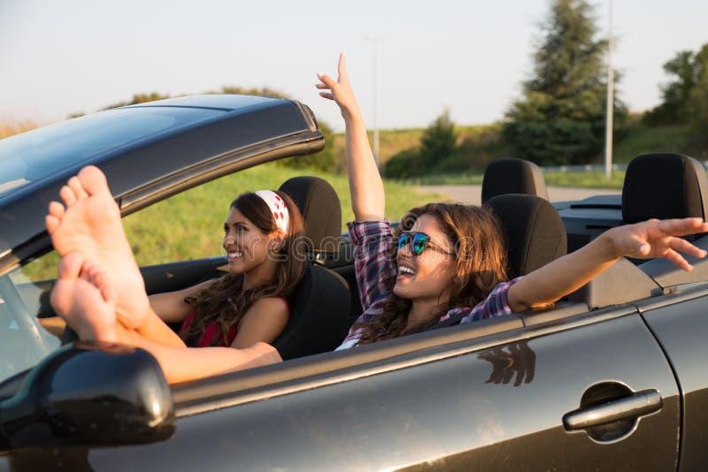 Duas jovens mulheres bonitas que conduzem ao redor em um carro convertível imagem de stock royalty free