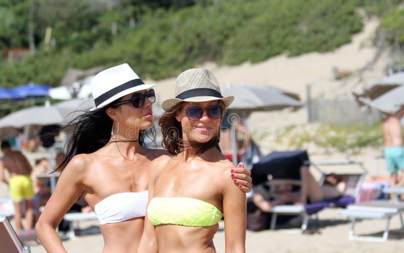 Duas jovens mulheres bonitas que dão uma volta em uma praia Amigos fêmeas que andam na praia e que riem em um dia de verão, aprec fotos de stock royalty free