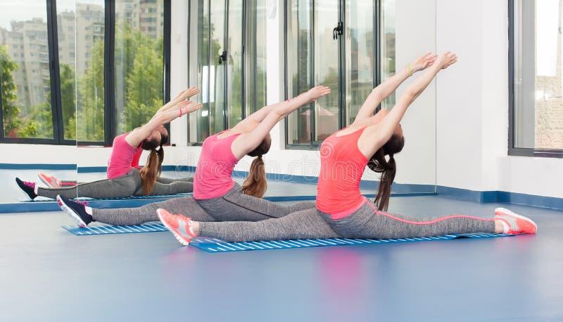 Duas jovens mulheres bonitas que fazem o exercício da ginástica imagens de stock