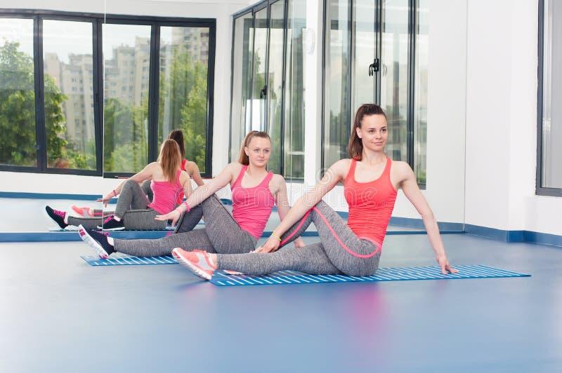 Duas jovens mulheres bonitas que fazem o exercício da ginástica fotos de stock royalty free