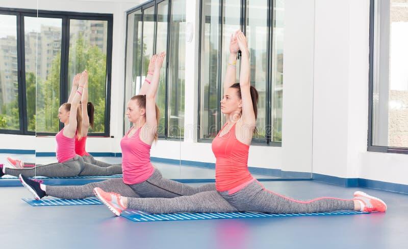 Duas jovens mulheres bonitas que fazem o exercício da ginástica imagem de stock