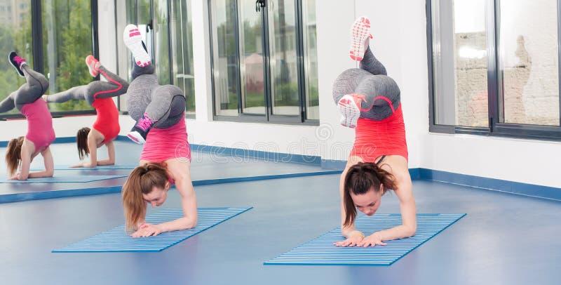 Duas jovens mulheres bonitas que fazem o exercício da ginástica foto de stock