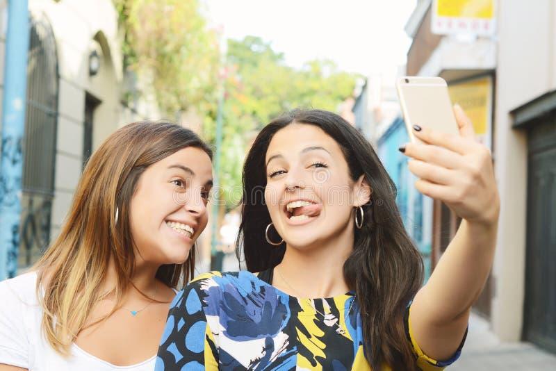 Duas jovens mulheres bonitas que fazem o selfie e que fazem caretas fotografia de stock royalty free