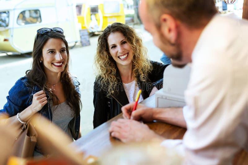 Duas jovens mulheres bonitas que pedem o alimento do cozinheiro de um caminhão do alimento fotos de stock