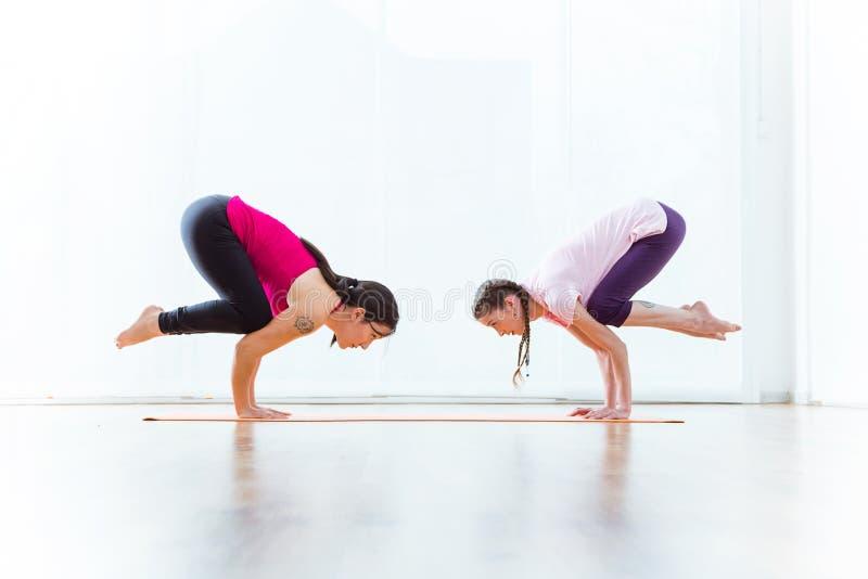 Duas jovens mulheres bonitas que praticam a ioga em casa fotografia de stock royalty free