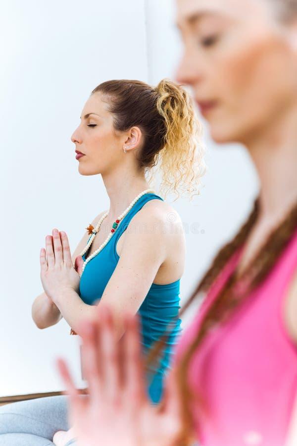 Duas jovens mulheres bonitas que praticam a ioga em casa imagem de stock royalty free