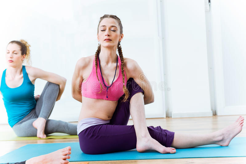Duas jovens mulheres bonitas que praticam a ioga em casa Marichyasana fotografia de stock royalty free