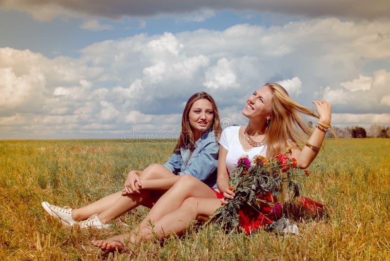 Duas jovens mulheres bonitas que sentam-se no prado do verão fotografia de stock royalty free