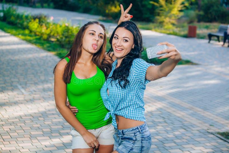 Duas jovens mulheres bonitas que usam o telefone esperto fotografia de stock royalty free