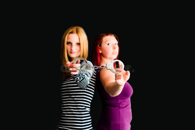 Duas jovens mulheres com algemas fotografia de stock royalty free