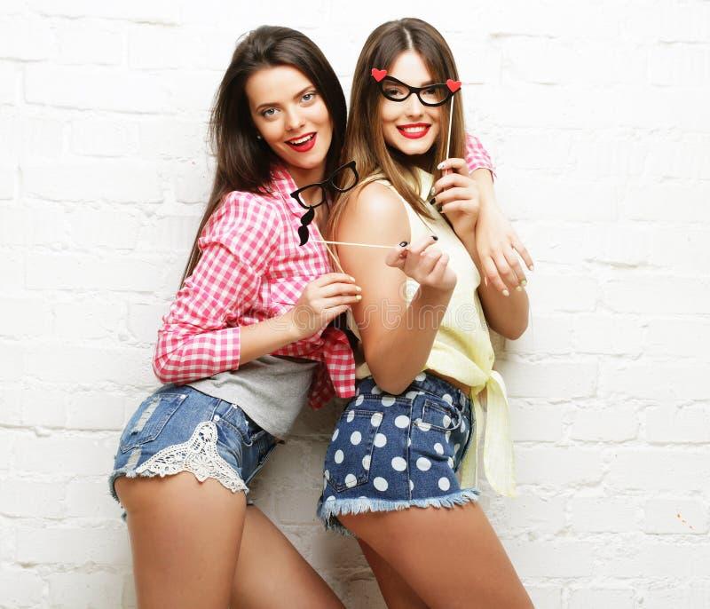 Duas jovens mulheres com os vidros do partido que tomam o selfie fotos de stock