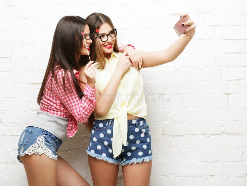 Duas jovens mulheres com os vidros do partido que tomam o selfie foto de stock royalty free