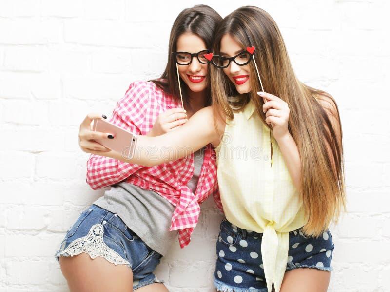 Duas jovens mulheres com os vidros do partido que tomam o selfie foto de stock