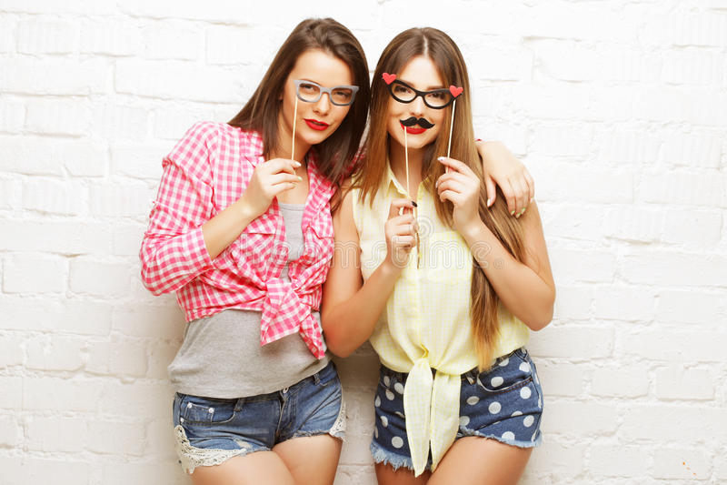 Duas jovens mulheres com os vidros do partido que tomam o selfie fotos de stock royalty free