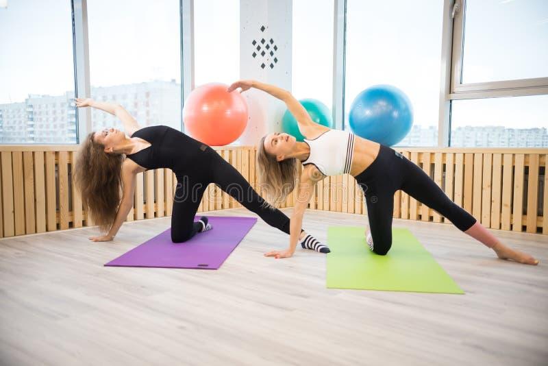 Duas jovens mulheres do atleta que fazem exerc?cios da ioga no gym imagem de stock