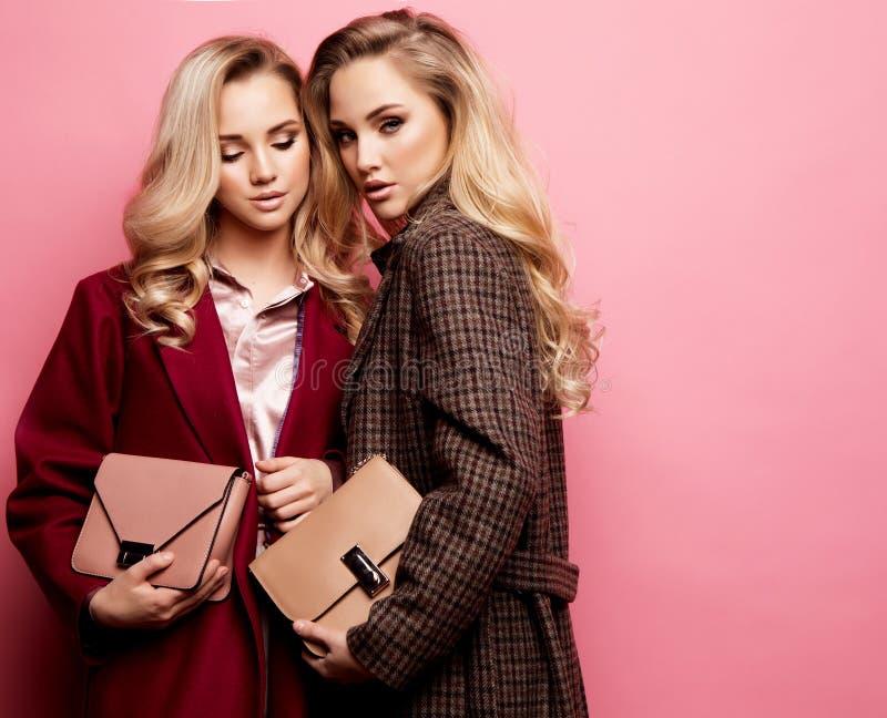 Duas jovens mulheres doces que levantam na roupa agradável, revestimento, bolsa Irmãs, gêmeos Foto da forma da mola foto de stock