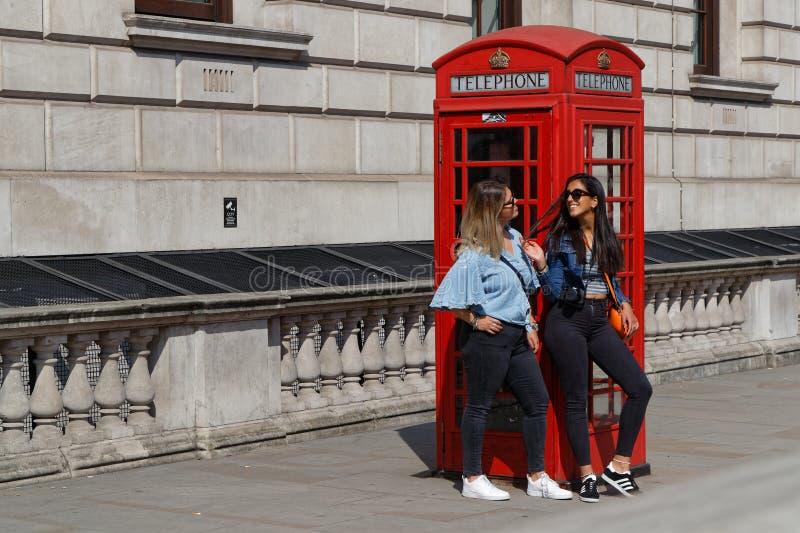 Duas jovens mulheres e uma cabine de telefone vermelha fotografia de stock