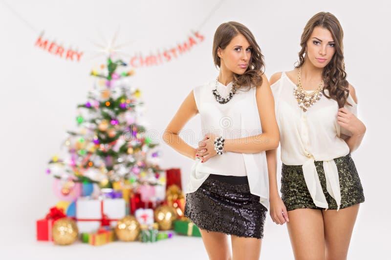 Duas jovens mulheres elegantes que comemoram o Natal imagens de stock