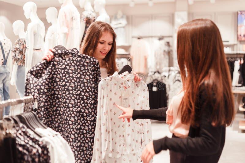 Duas jovens mulheres estão escolhendo uma camisa do verão na loja da forma fotos de stock royalty free