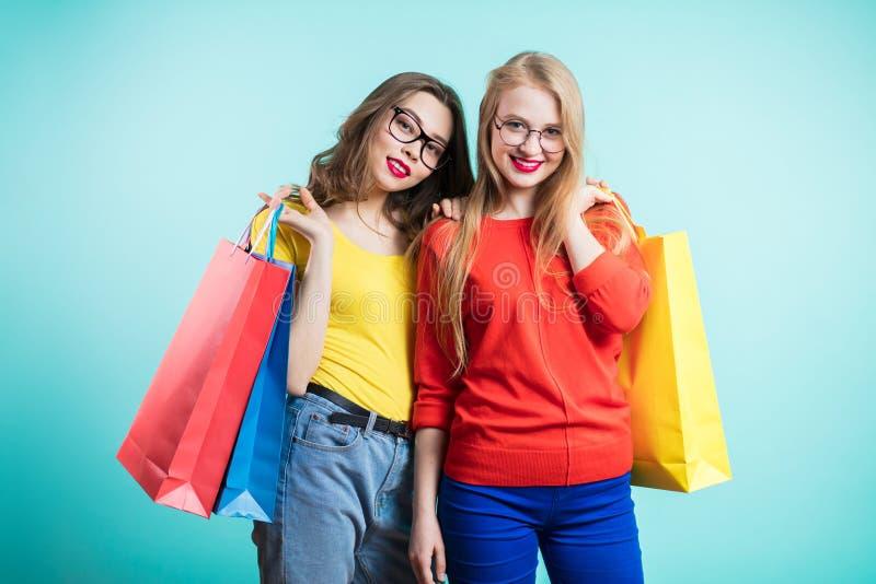 Duas jovens mulheres felizes com os sacos de compras no fundo azul olham com sorriso imagens de stock