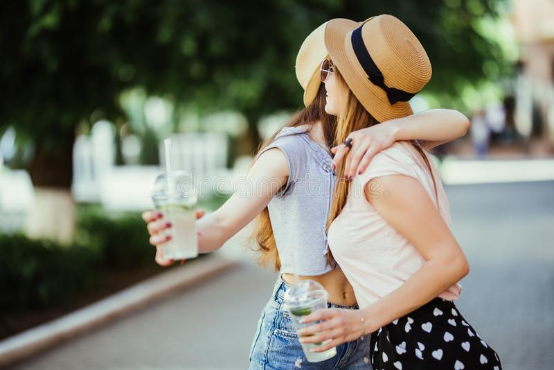 Duas jovens mulheres felizes que abraçam e que riem horas de verão do ar livre imagens de stock royalty free
