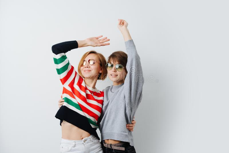 Duas jovens mulheres felizes, sorrindo bonitas que abraçam, dança junto imagem de stock royalty free