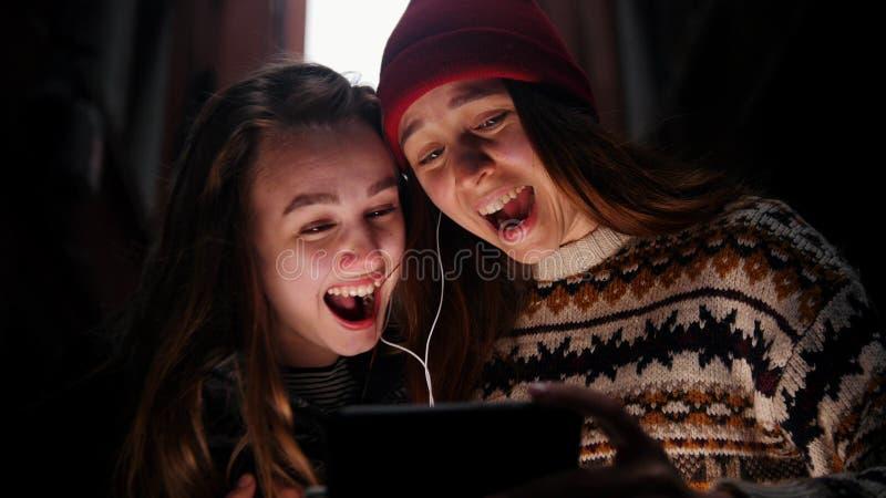 Duas jovens mulheres na aleia estreita Eles que olham no telefone e no riso fotos de stock royalty free