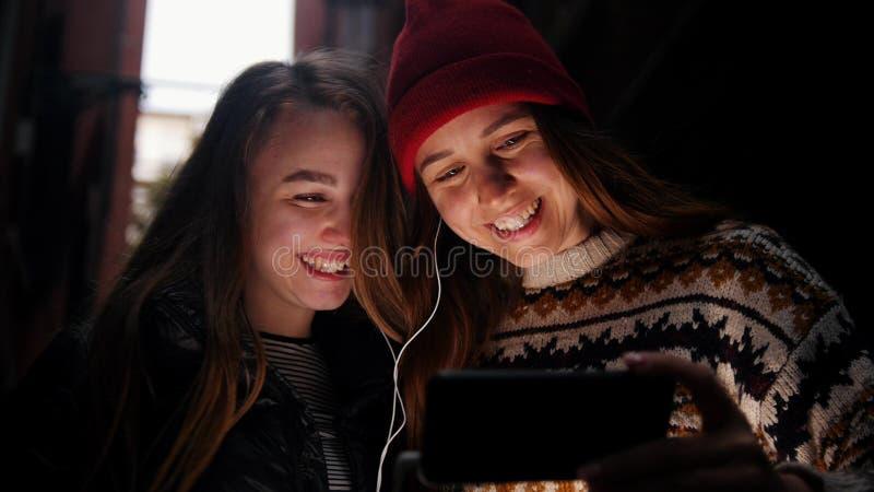 Duas jovens mulheres na aleia estreita O telefone destaca suas caras imagens de stock