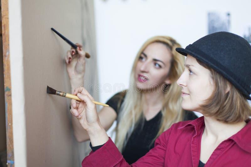 duas jovens mulheres no desenho e no curso de pintura imagens de stock royalty free