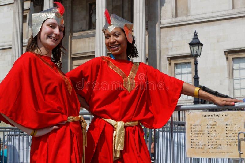 Duas jovens mulheres no vermelho na festa de St George fotografia de stock royalty free