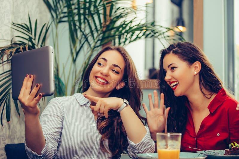 Duas jovens mulheres que acenam a mão em linha durante uma chamada video com uma tabuleta imagem de stock